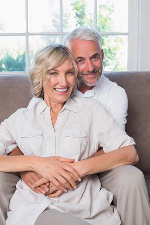 自宅のリビング ルームで女性を後ろから抱きしめる中年の男性の肖像画 写真素材