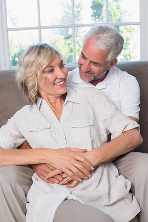 Portrait of a mature man embracing woman from behind in the living room at home Фото со стока