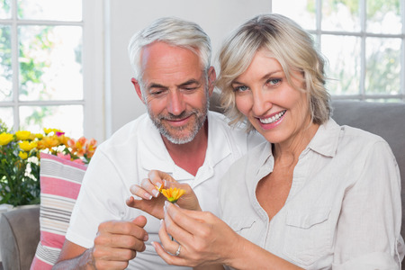 Happy mature couple with a flower in the living room at home Фото со стока