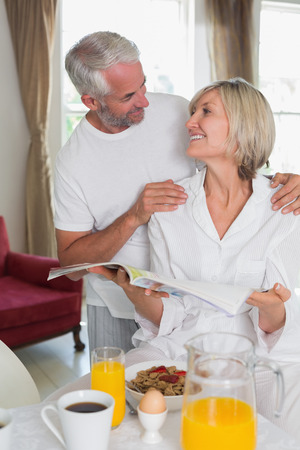 Mature couple reading newspaper while having breakfast at home Фото со стока