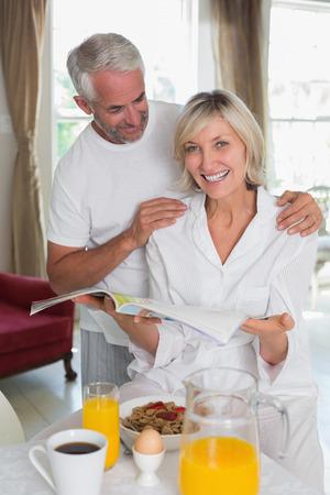 成熟したカップルの家で朝食をとりながら新聞を読む 写真素材