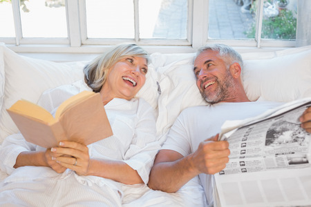 Cheerful mature couple with newspaper and book lying in bed at home photo