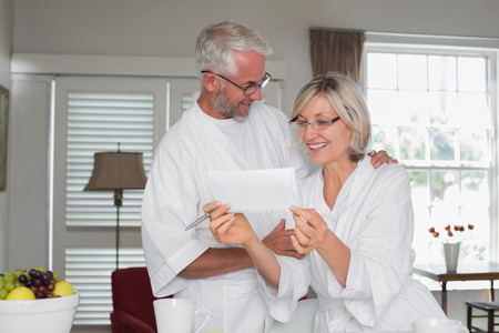 Cheerful casual mature couple looking at a document at home Фото со стока