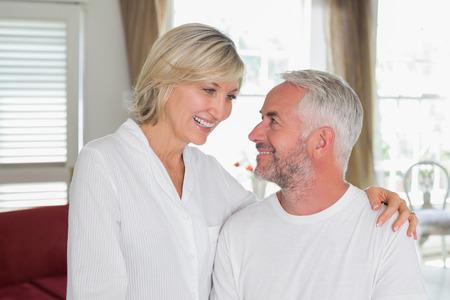 自宅の居間で見てお互い幸せな熟年カップル 写真素材