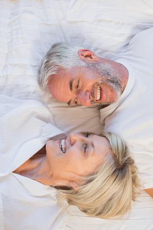 自宅のベッドで横になっている幸せな熟年カップルの高角度の肖像画 写真素材