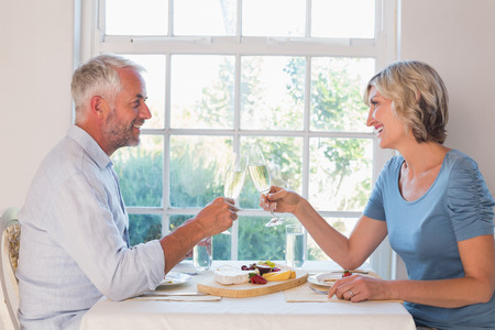 Side view of a mature couple toasting drinks over food by the window at home