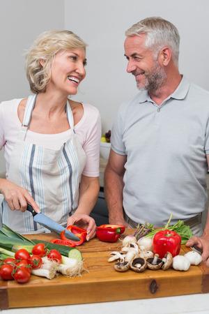 自宅のキッチンで一緒に食糧を準備する幸せな熟年カップル