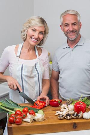 幸せな熟女カップルは、自宅のキッチンで食事の準備の肖像画