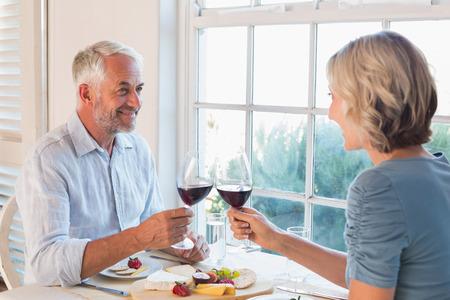 自宅の窓による食品を飲む幸せな熟年カップル乾杯 写真素材
