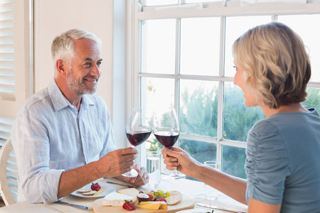 Happy mature couple toasting drinks over food by the window at home Фото со стока