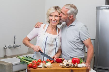 中年の男性が女性にキス、彼女は自宅の台所で野菜を切る 写真素材