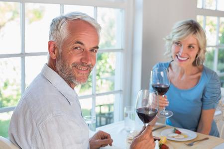 自宅窓際食品を持つワイングラスを持つ成熟したカップルの肖像画