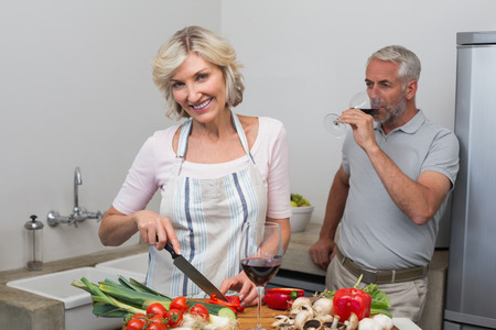 Mature man with wine glass and woman chopping vegetables in the kitchen at home