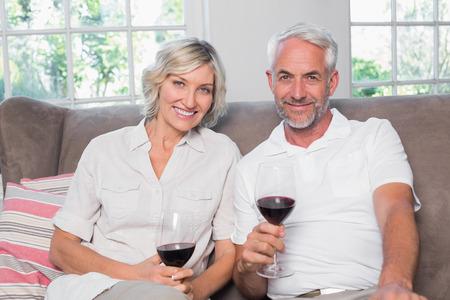 自宅のリビング ルームでガラスのワインと幸せなリラックスした大人のカップルの肖像画