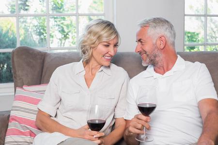 ワインと幸せなリラックスした大人のカップルは、自宅のリビング ルームでメガネします。
