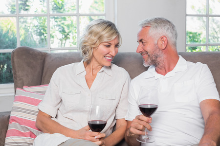 Happy relaxed mature couple with wine glasses in the living room at home Фото со стока