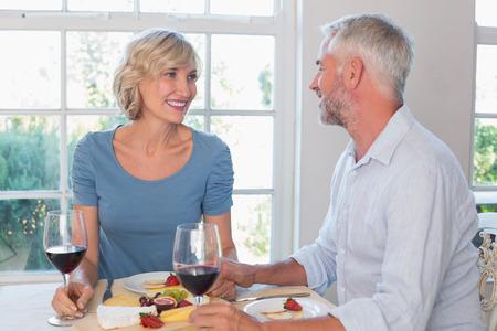 食品を家庭で持っているワイングラスを持つ幸せな熟年カップルの肖像画