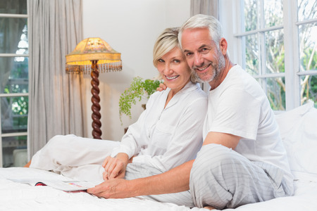 Side view portrait of a relaxed happy mature couple with book in bed at home Фото со стока