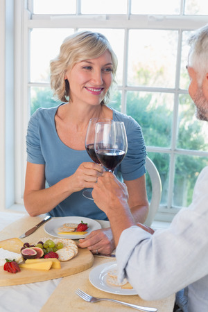Portrait of a mature couple toasting wine glasses over food at home