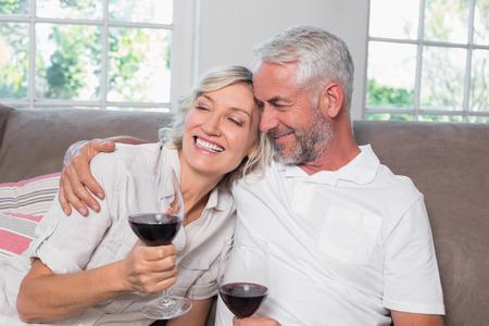 ワインと幸せな愛情のある成熟したカップルは、自宅のリビング ルームでメガネします。