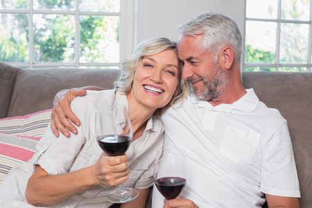 Happy loving mature couple with wine glasses in the living room at home