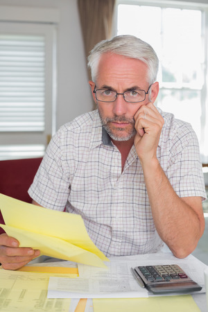 Serious mature man sitting with home bills and calculator at table Stock Photo - 28072709