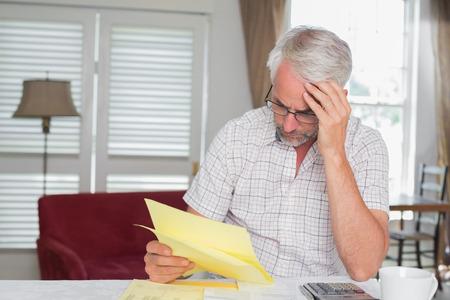 ホーム手形とテーブルで電卓に座っている深刻な成熟した男 写真素材