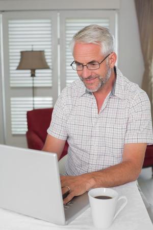 家でノート パソコンを使用して笑みを浮かべてカジュアルな成熟した男 写真素材
