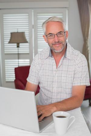 家でノート パソコンを使用して笑みを浮かべてカジュアルな成熟した男の肖像