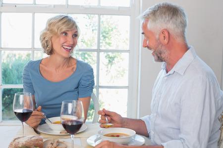 自宅の窓に食品を持つワイングラスを持つ成熟したカップル