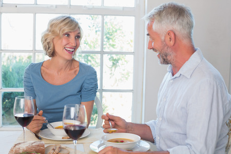 Mature couple with wine glasses having food against the window at home