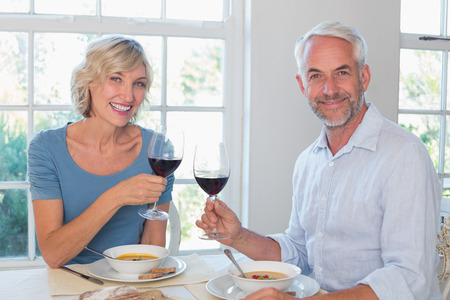 Happy mature couple toasting wine glasses over food against the window at home Фото со стока