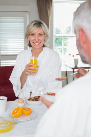 自宅トリミング男と朝食を食べて笑顔の成熟した女性の肖像画 写真素材
