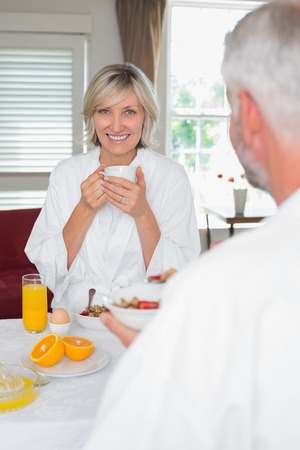 Portrait of a smiling mature woman having breakfast with cropped man at home