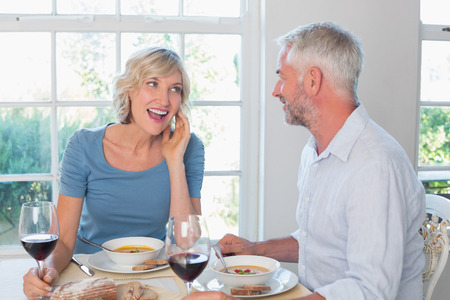 Happy mature couple with wine glasses having food at home