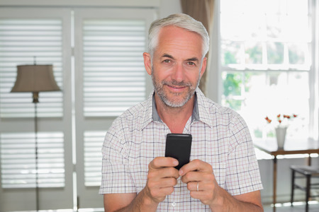 リラックスした中年の男性の笑顔付きテキスト メッセージング自宅の肖像画 写真素材