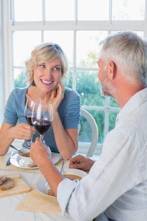 自宅の窓に食品を飲む幸せな熟年カップル乾杯 写真素材