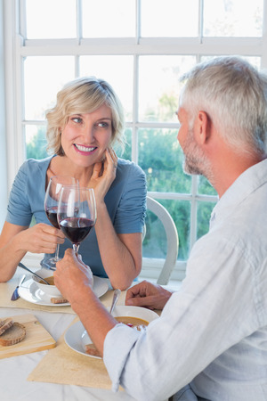 Happy mature couple toasting drinks over food against the window at home