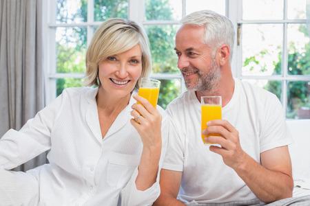 オレンジ ジュースを家庭で保持している幸せな熟年カップルの肖像画
