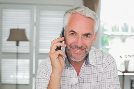 家で携帯電話を使用してリラックスした中年の男性の肖像画 写真素材