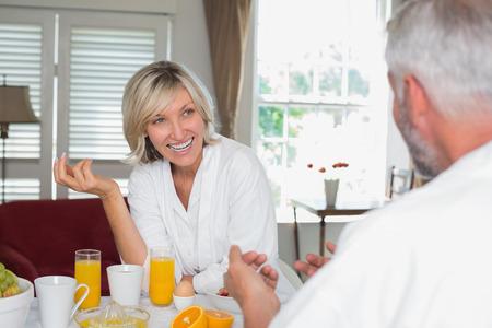 自宅トリミング男と朝食を持つ陽気な成熟した女性 写真素材