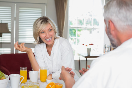 Cheerful mature woman having breakfast with cropped man at home