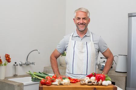 自宅のキッチンで野菜の成熟した男の肖像