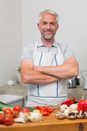 Portrait of a mature man with vegetables in the kitchen at home