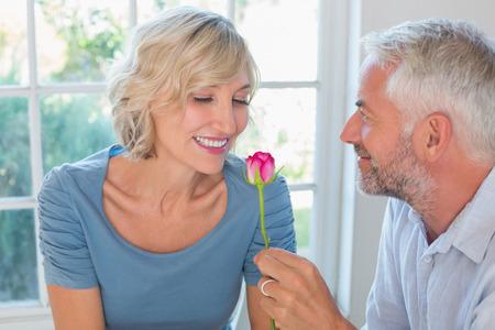 自宅の窓に花と幸せな熟年カップル 写真素材