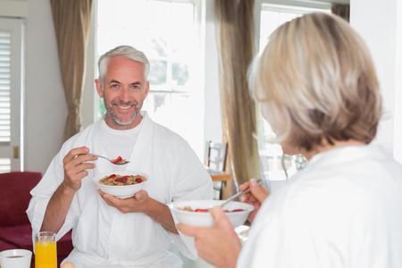 自宅トリミング女性と朝食を食べて笑顔の中年の男性の肖像画 写真素材