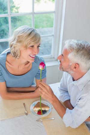 High angle view of a mature man giving flower to a happy woman Фото со стока