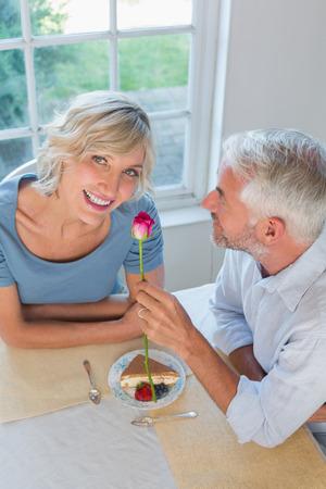 幸せな女性に花を与える成熟した男の高角度の肖像画 写真素材