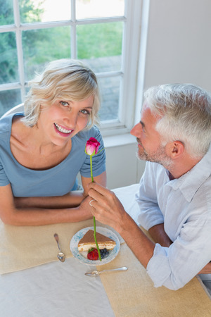 High angle portrait of a mature man giving flower to a happy woman