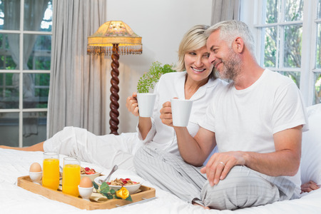 Portrait of a smiling mature couple with coffee cups sitting on bed at home photo